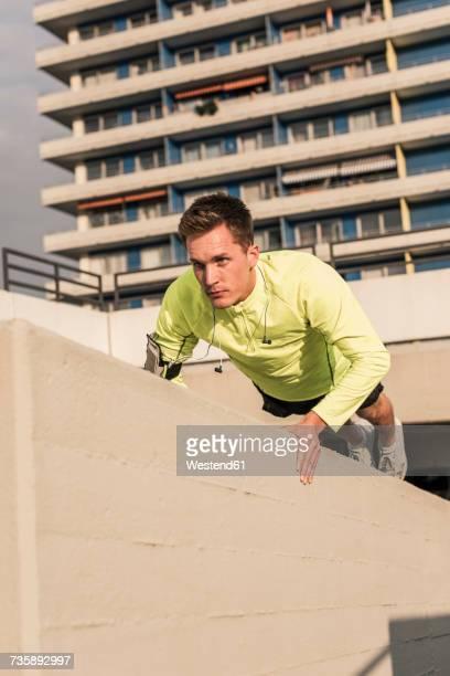Young athlete exercising push ups on parking level