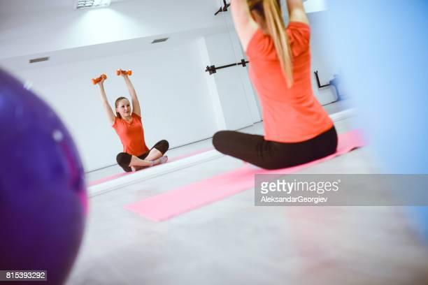 Jeune athlète féminine pratiquant Pilates avec des poids dans le gymnase