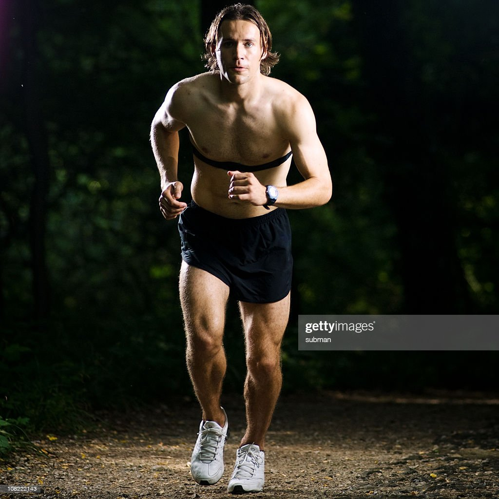 Young athlete running in woods : Stock Photo