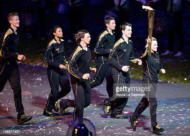 A young athlete who is joined by six others who present Britain's hopes for the next Olympics carries the Olympic flame during the Opening Ceremony...