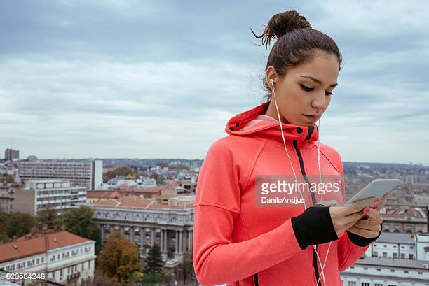 young athlete woman using her smartphone after workout