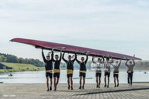 Young athletes carrying a crew row boat over heads
