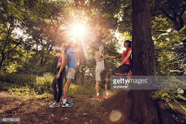 Young athletes having a break from exercising in nature.