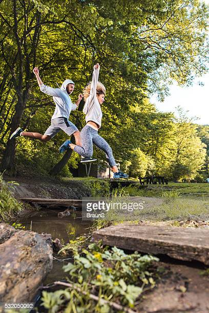 Young athletes jumping over the stream in the park.