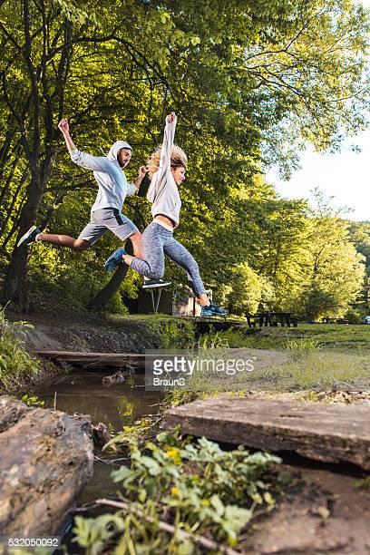 Junge Sportler springen über den stream im park.