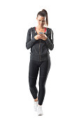 Young athletic female runner in sportswear using cell phone. Full body length portrait isolated on white background.