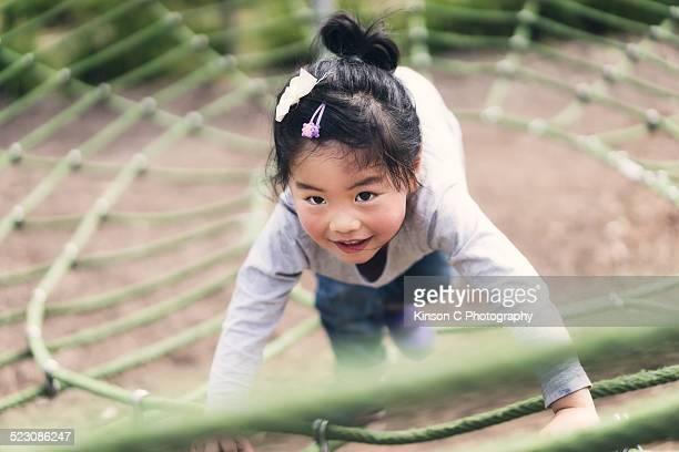 Young athletic girl climbs green ropes at park