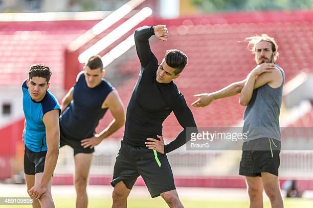 Athlétique jeune homme échauffement avant de faire de l'exercice sur le stade.