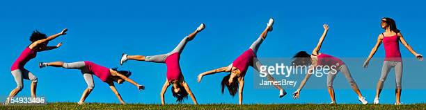 Young Athletic Woman Doing Cartwheel on Hilltop