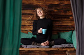 Young athletic curly woman is drinking tea after yoga training