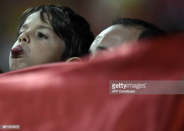 A young Atletico fan stick out his tongue before the Spanish league football match Club Atletico de Madrid vs FC Barcelona at the Wanda Metropolitano...