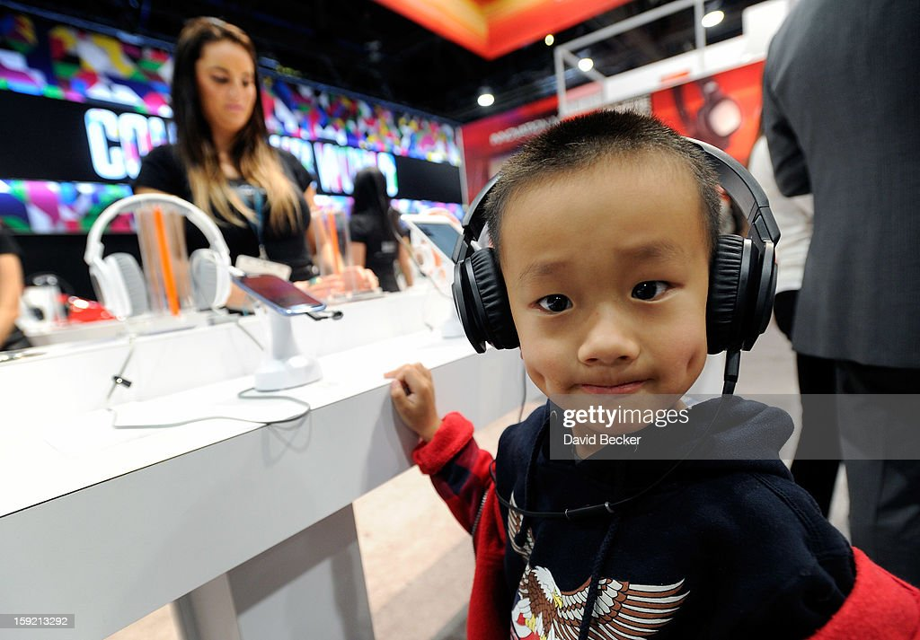 A young attendee listens to music on a pair of JBL J88i headphones at the Harman-Kardon booth at the 2013 International CES at the Las Vegas Convention Center on January 9, 2013 in Las Vegas, Nevada. CES, the world's largest annual consumer technology trade show, runs through January 11 and is expected to feature 3,100 exhibitors showing off their latest products and services to about 150,000 attendees.