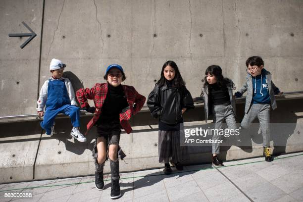 Young attendees of Seoul Fashion Week pose for photographers during Seoul Fashion Week at Dongdaemun Design Plaza in Seoul on October 19 2017 For...