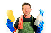 young attractive and happy domestic house husband or single man holding sponge and detergent spray in washing gloves smiling cheerful in home cleaning service work and lifestyle concept