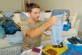 young attractive and happy man at home couch preparing travel back and packing suitcase folding clothes and organizing passport and things before leaving on holidays trip and travel concept