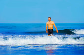 young attractive and happy man with beard and swimming trunks at tropical paradise desert beach alone playful and cheerful in sea water enjoying Summer holidays destination isolated blue