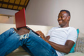 young attractive and happy successful black African American man networking with laptop computer at living room couch smiling cheerful and satisfied in internet business success concept