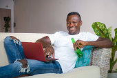 young attractive and happy successful black African American man networking with laptop computer at living room couch smiling cheerful drinking beer bottle  in internet business success concept