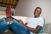 young attractive and happy successful black afro American man networking with laptop computer at living room couch smiling cheerful and satisfied in internet business success concept