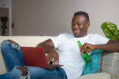 young attractive and happy successful black afro American man networking with laptop computer at living room couch smiling cheerful drinking beer bottle  in internet business success concept