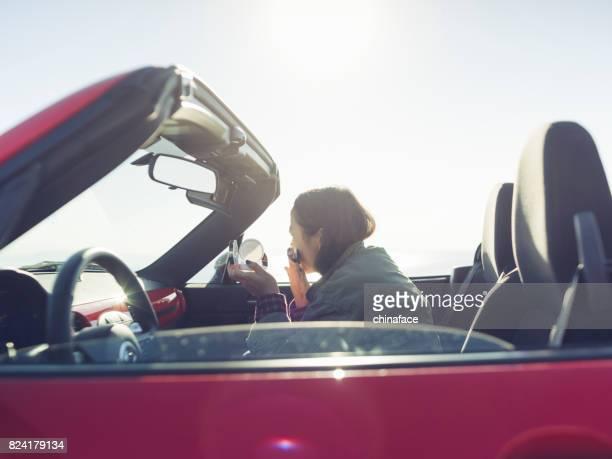 jeune femme asiatique attrayante qui composent dans une Cabriolet rouge