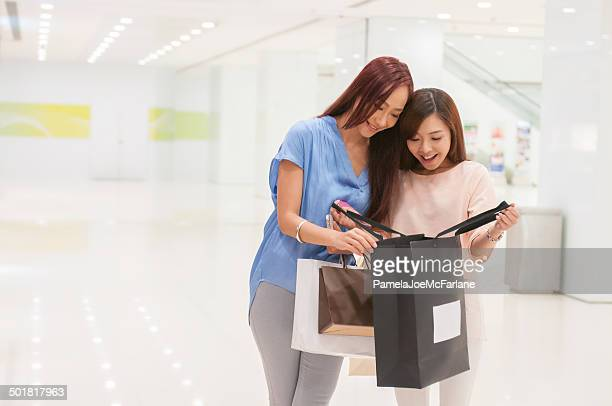 Young, Attractive Asian Women Looking at Purchases