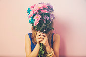 Young attractive beautiful woman smelling flowers.