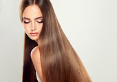 Young attractive girl-model with gorgeous, shiny, long, straight hair. Good and healthy hair as result of right care.
