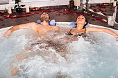 Young attractive couple relax in hot tub in spa center