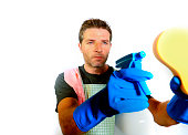 young attractive domestic house husband or single man holding sponge and detergent spray in washing gloves cleaning towards the camera in home cleaning service work lifestyle