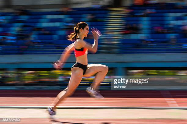 Young attractive female athlete at long jump, pannig shot