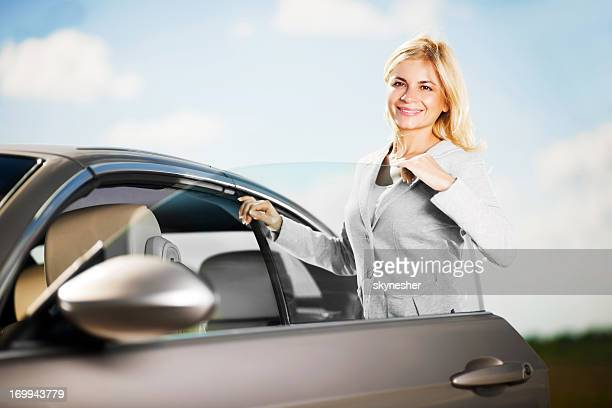 Young attractive female is opening her car door.