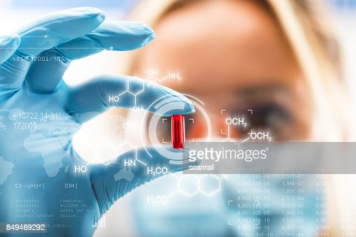 Young attractive female scientist holding a red transparent pill : Stock Photo
