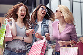 Three beautiful girls with shopping bags in the city.People,sale,shopping,fun and happiness concept.