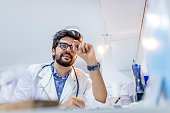 Young attractive male scientist holding a  pill. Male doctor holding a pill. Pharmacist holding a pill. Hand of a hospital medical expert shows the pill to be taken to his patient. concept of generica