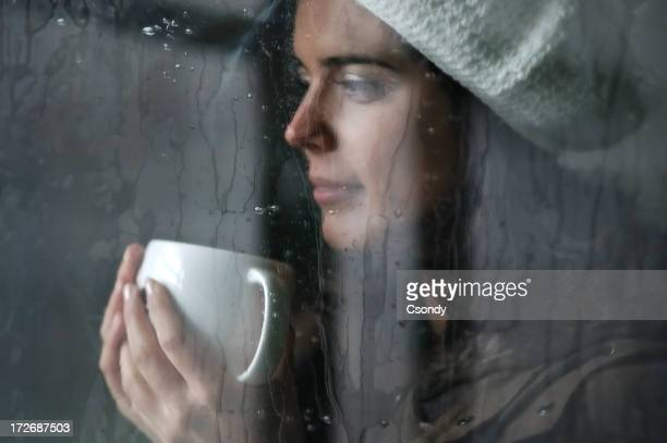 Young attractive woman behind a rainy window
