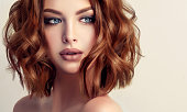 Beautiful model brunette with middle length curled hair, bright make up and purple manicure. Glamour evening hairdress. Short wavy hairstyle and pink manicure.