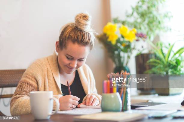 Young attractive woman drawing in adult coloring book at table