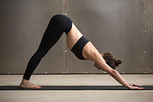 Young attractive yogi woman practicing yoga, standing in adho mukha svanasana exercise, Downward facing dog pose, working out, wearing black sportswear, cool urban style, full length, grey studio