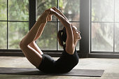 Young attractive sporty woman practicing yoga at home, stretching in Dhanurasana exercise, Bow pose, working out, wearing sportswear, black shorts and top, indoor full length, studio background