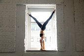 Young attractive woman practicing yoga, standing on window sill in Adho Mukha Vrksasana exercise, Downward facing Tree Pose pose, working out, wearing sportswear, black pants, top, indoor full length