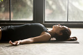 Young attractive woman practicing yoga at home, lying in Savasana exercise, Corpse pose, working out, wearing sportswear, black shorts and top, indoor close up image, studio background, side view
