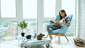 Young attractive woman read book sitting on balcony in modern loft apartment