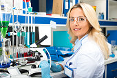Young attractive woman scientist in protective glasses and gloves researching in the scientific chemical laboratory