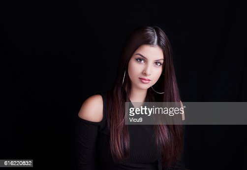 Young attractive woman with long hair on black background. : Stock-Foto