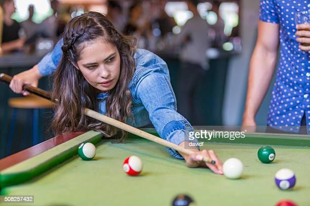 Junge australische First Nations Frau spielt Schwimmbad in einer Bar