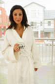 A young Australian woman in her white dressing gown holds a coffee mug in a typical suburban setting at home. Happy and casual