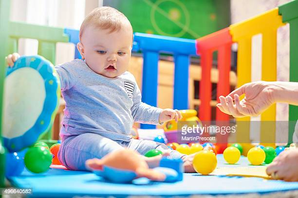 Young baby boy playing with his toys in playpen