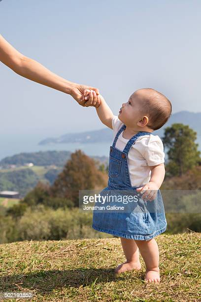 Young baby standing and holding mothers hand