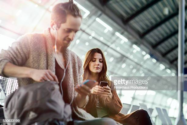 Young Backpacker Couple Texting At Airport